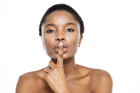 over black: Afro american woman showing finger over lips isolated on a white background Stock Photo
