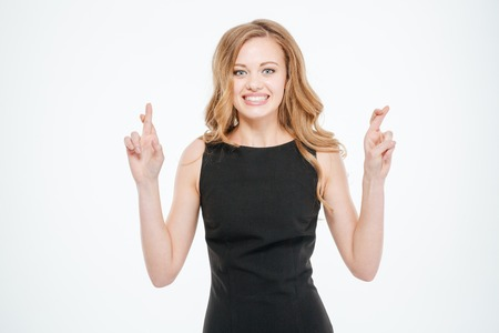 fingers: Woman standing with crossed fingers isolated on a white background Stock Photo