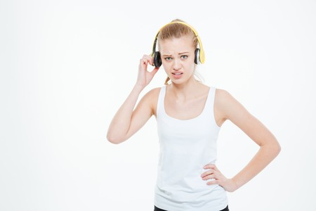 refusing: Unhappy stressed young woman listening to music too loud and removing yellow headphones over white background Stock Photo