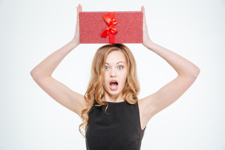 anticipated: Amazed woman holding gift box on the head isolated on a white background Stock Photo
