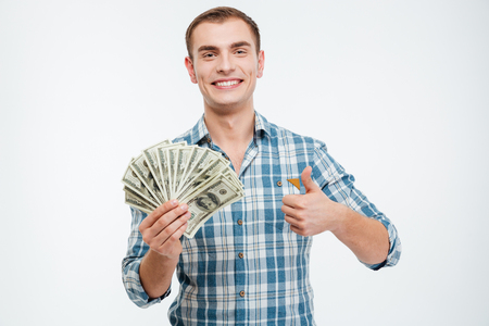 man holding money: Cheerful successful young man holding money and showing thumbs up over white background