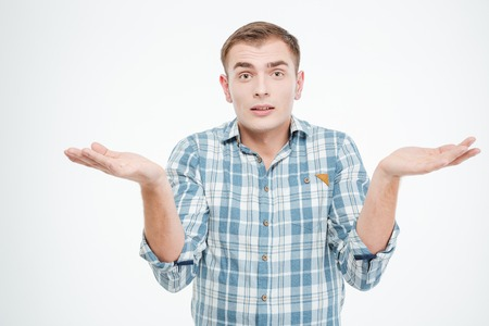 forgetful: Confused handsome young man holding copuspace on both palms over white background