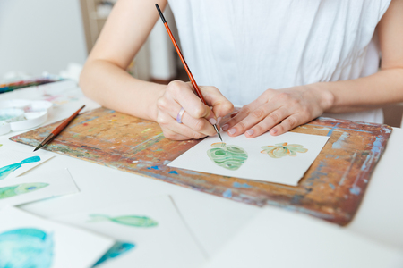 Nahaufnahme der Hände der Frau Künstler mit Pinsel und Aquarellfarben auf dem Tisch Malerei Standard-Bild - 55141194