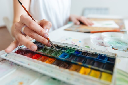 Closeup of set of watercolor paints used by woman artist on the table in workshop