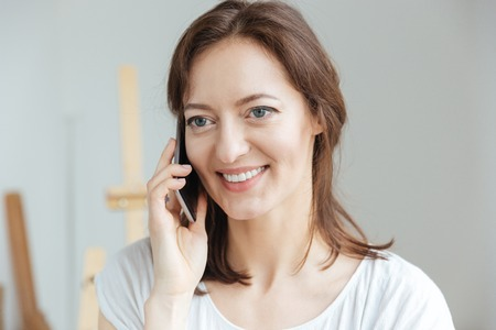 Happy attractive woman artist smiling and talking on mobile phone in workshop Stock fotó