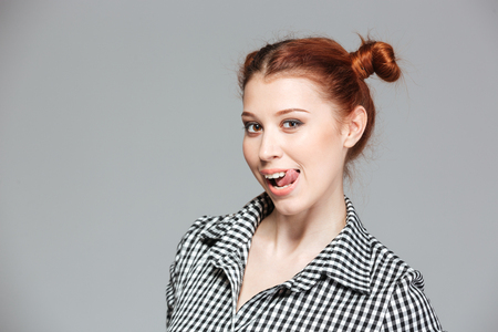 Portrait of cute playful young woman showing tongue over grey background