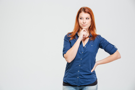 reflect: Pensive lovely smiling redhead young woman thinking over white background