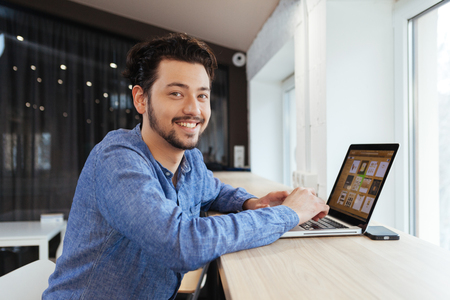 clothes interesting: Smiling casual businessman using laptop computer and looking at camera in office