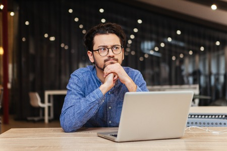 clothes interesting: Pensive man sitting at the table with laptop computer in office Stock Photo