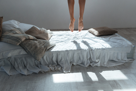 bedsheets: Slim legs of young woman flying in the air above bed in bedroom