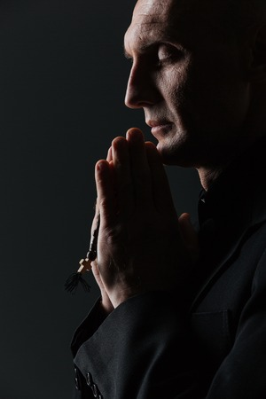 priesthood: Man with eyes closed holding rosary and praying over black background