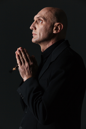 sotana: Perfil del hombre hermoso que sostiene el rosario y la oración sobre el fondo negro
