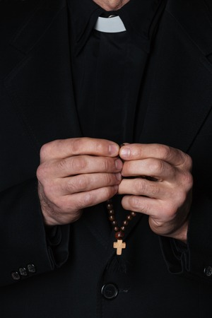 over black: Hands of catholic priest holding rosary over black background