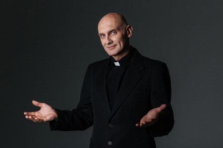 priesthood: Smiling priest standing and inviting you over black background
