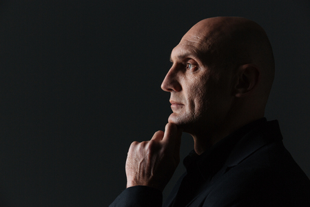 Profile of thoughtful attractive businessman thinking and  touching his chin over black background