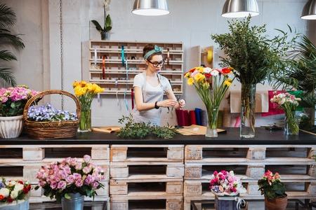 Schattige geconcentreerde jonge vrouwelijke bloemist in glazen werken in bloemenwinkel