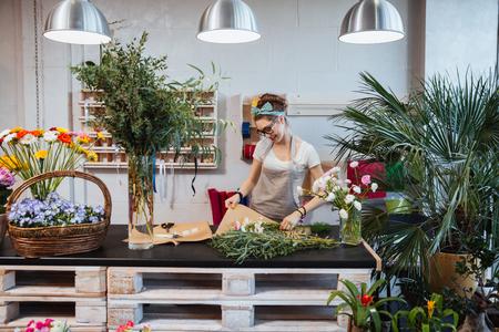 Cheerful cute young woman florist enjoying creating bouquet in flower shop