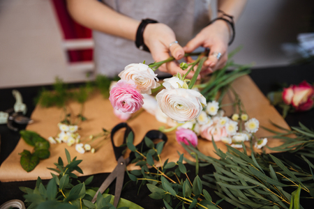 Closeup of hands of young woman florist creating bouquet of pink roses on the table Stock Photo