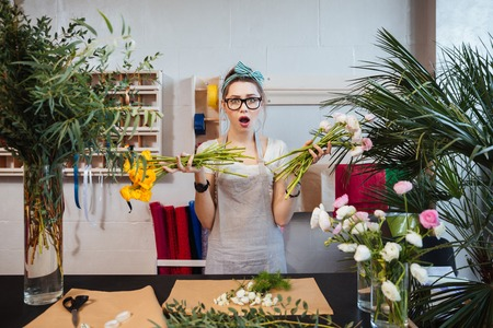 shoked: Amazed shoked young woman florist designing bouquet and holding two bunches of flowers Stock Photo