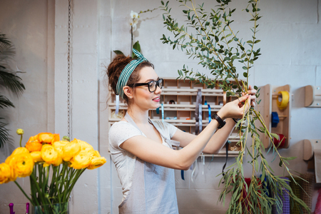 arranging: Smiling lovely young woman florist arranging plants in flower shop