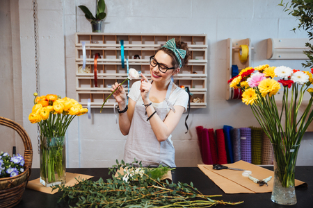 Gelukkig schattige jonge vrouw bloemist genieten van witte roos in bloemenwinkel