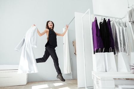 interrior: Cheerful woman jumping in clothing store Stock Photo