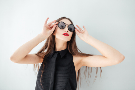 Charming woman with sunglasses posing isolated on a white background