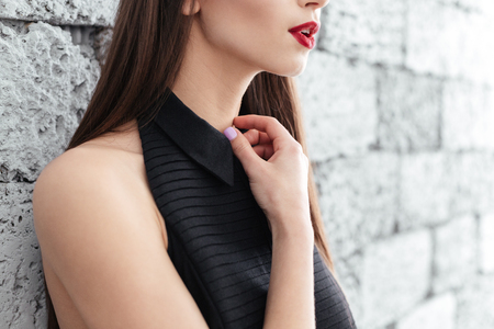 cropped: Cropped image of a woman leaning on brick wall