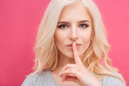 Pretty woman showing finger over lips on pink background