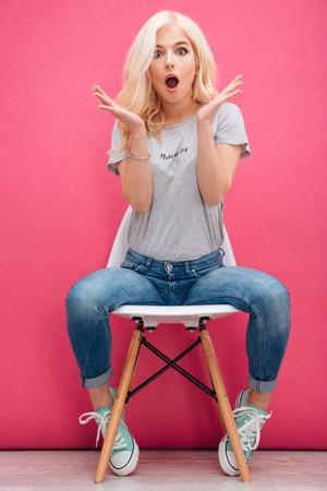 Amazed charmante femme assise sur la chaise sur fond rose Banque d'images - 56616156