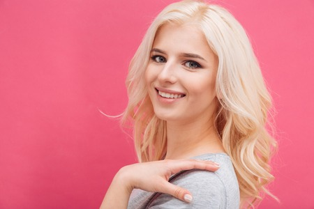 Smiling lovely woman looking at camera over pink background