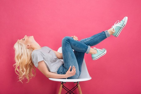 Attractive woman having fun on the chair over pink background Standard-Bild