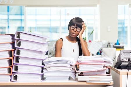Vermoeid Afro-Amerikaanse zakenvrouw zitten aan de tafel met veel werk in het kantoor