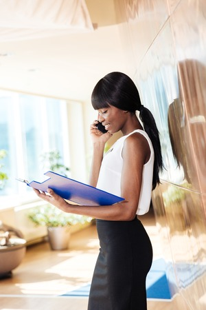 clothes organizer: Beautiful afro american businesswoman reading papers and talking on the phone in office Stock Photo