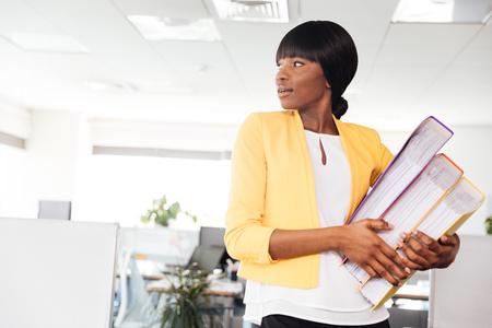 Empresaria afroamericana que sostiene carpetas y que mira lejos en oficina Foto de archivo