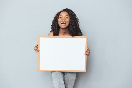 Cheerful afro american woman showing blank board over gray background Reklamní fotografie