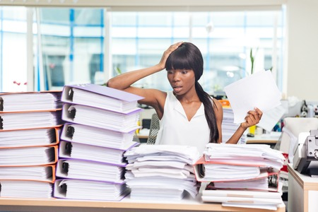 busy person: Shocked afro american businesswoman sitting at the table with many papers in office Stock Photo