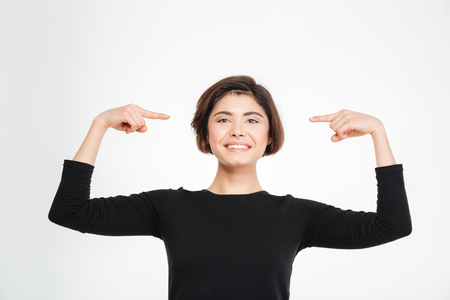 egocentric: Smiling woman pointing finger at herself isolated on a white background Stock Photo