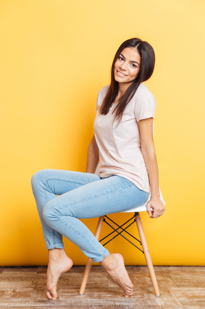 Full length portrait of a smiling cute woman sitting on the chair over yellow background
