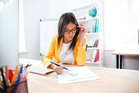 charming businesswoman: Charming businesswoman working with paper in office Stock Photo
