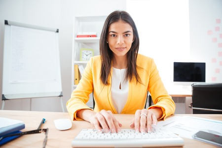 charming businesswoman: Happy charming businesswoman typing on keyboard in office