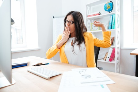 cansancio: Empresaria joven que bosteza en la oficina