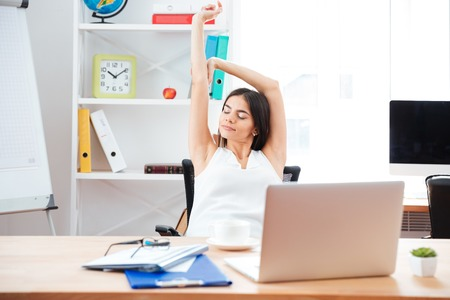 charming businesswoman: Young charming businesswoman stretching hands in office Stock Photo