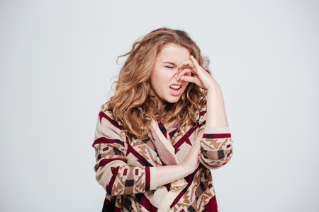unbearable: Woman with disgust emotion standing isolated on a white background Stock Photo