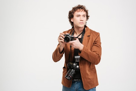 looking away from camera: Male reporter holding camera and looking away isolated on a white background