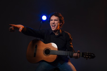 somebody: Happy man with guitar pointing finger on somebody over dark background Stock Photo