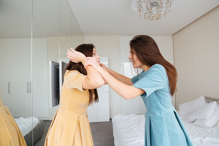 irritated: Two mad irritated young sisters twins standing and arguing in bedroom Stock Photo