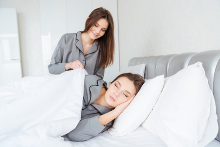 aring: Smiling lovely young woman in grey pajamas covering her sleeping sister twin with white duvet Stock Photo