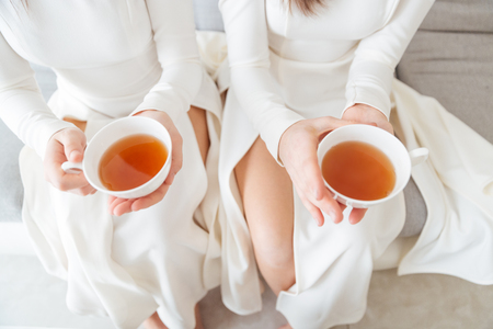 women friendship: Top view of two attractive women in white dresses sitting and holding two cups of tea Stock Photo