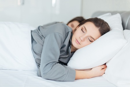twin house: Two pretty young women sleeping in bedroom together Stock Photo